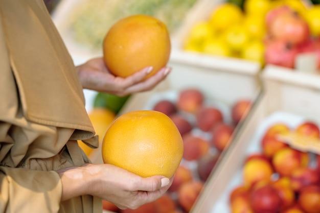 Ręce młodych kobiet kupującego trzymając świeże dojrzałe żółte grejpfruty przy wyborze, który z nich wziąć
