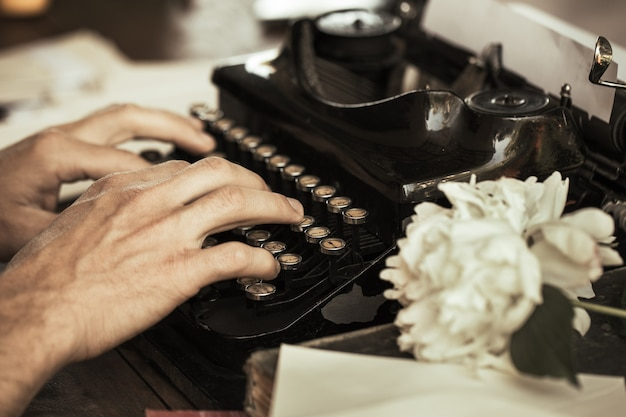 Ręce młodzieńca wpisując na zabytkowej maszynie do pisania