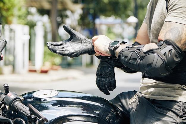 Ręce motocyklisty siedzącego na rowerze i zakładającego sprzęt jeździecki, taki jak ochraniacze na przedramiona i skórzane rękawiczki