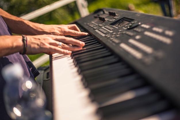 Ręce muzyka po mistrzowsku grają na klawiaturze podczas koncertu na żywo