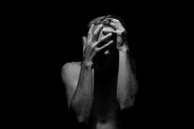 Ręce na głowie, czarno-białe dramatyczne zdjęcie mężczyzny