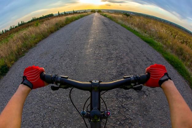 Ręce na kierownicy jadąc rowerzystą na drodze w kierunku zachodu słońca