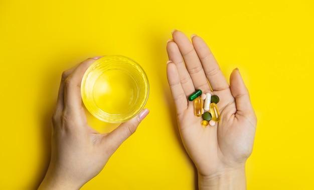 Ręce na żółtej powierzchni, pigułki leczące wodę wirusem. selektywne skupienie
