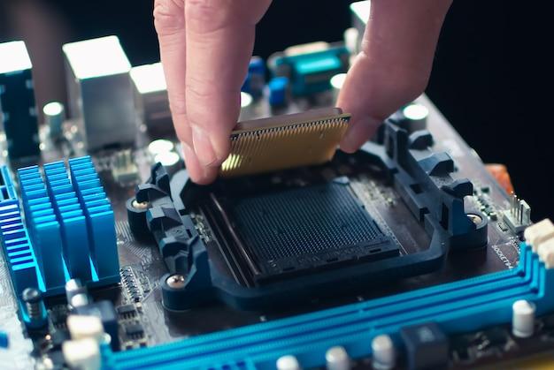 Ręce naprawiające płytę główną komputera lub laptopa z bliska w służbie