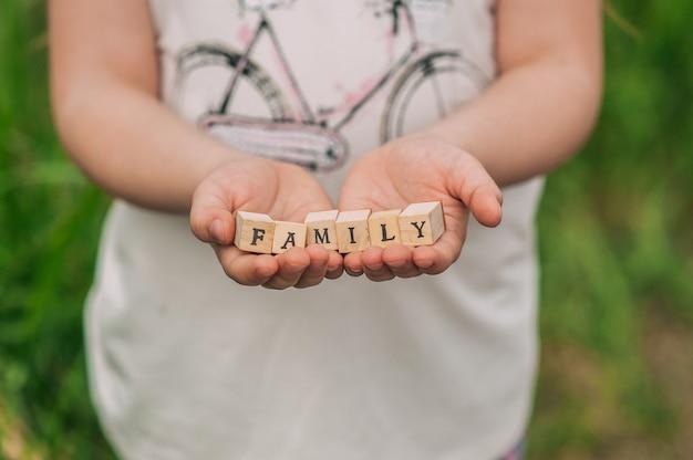 Ręce nastolatka trzymającego drewniane kostki z literami, które tworzą rodzinę napisów.