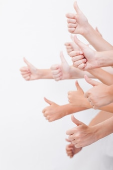 Ręce nastolatków pokazujące znak porządku na białym