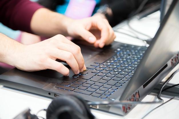 Ręce nie do poznania przycięte młody człowiek wpisując na komputerze przenośnym.