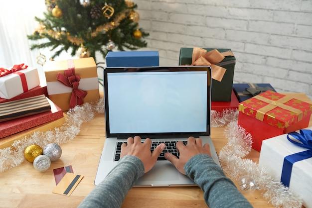 Ręce nierozpoznawalnego człowieka kupującego prezenty online
