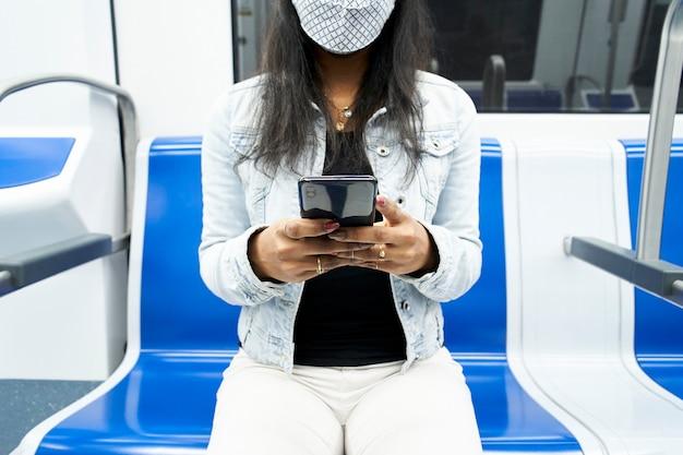 Ręce nierozpoznawalnej czarnej kobiety siedzącej w wagonie metra za pomocą smartfona