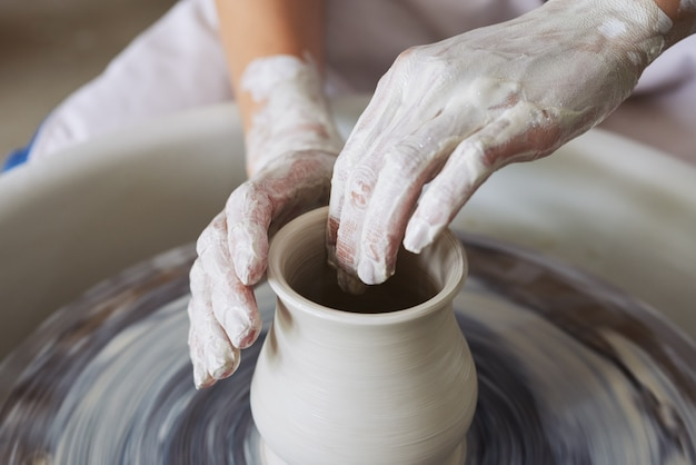 Ręce nierozpoznawalny żeński garncarz robi glinianą wazę na koło do rzucania
