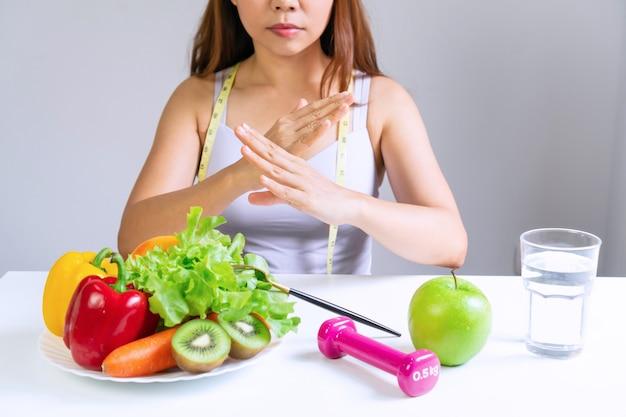 Ręce nieszczęśliwej kobiety aisan w podkoszulku, wykonującej znak, odmawiają warzywom i owocom znudzonej emocji na temat diety. koncepcja zdrowej żywności. ścieśniać