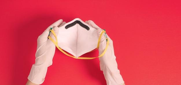 Ręce nosić rękawiczki medyczne i trzymać maskę n 95 na twarz. połóż na czerwonym tle.