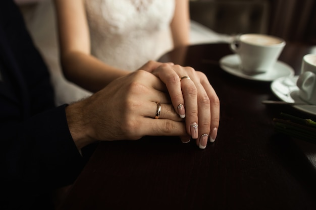 Ręce nowożeńców pary ze złotymi obrączkami ślubnymi