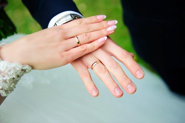Ręce nowożeńców z bliska. złote obrączki ślubne na palcu pary młodej, manicure ślubny. pojęcie uroczystości ślubnej.