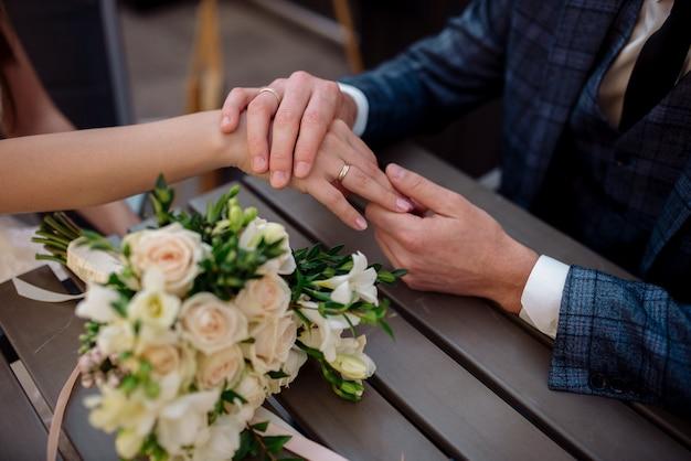 Ręce nowożeńców z obrączkami