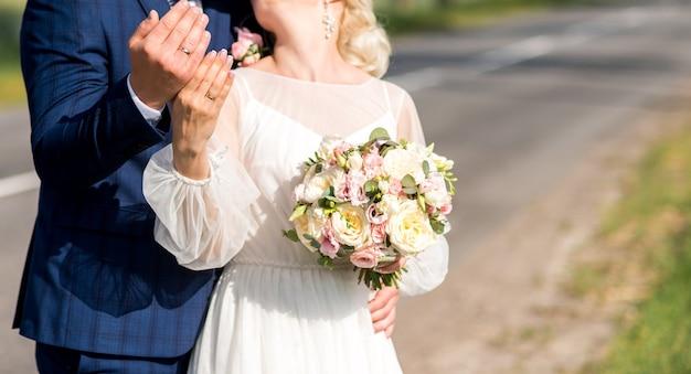 Ręce nowożeńców z pierścieniami. bukiet ślubny na tle dłoni młodej pary ze złotym pierścieniem
