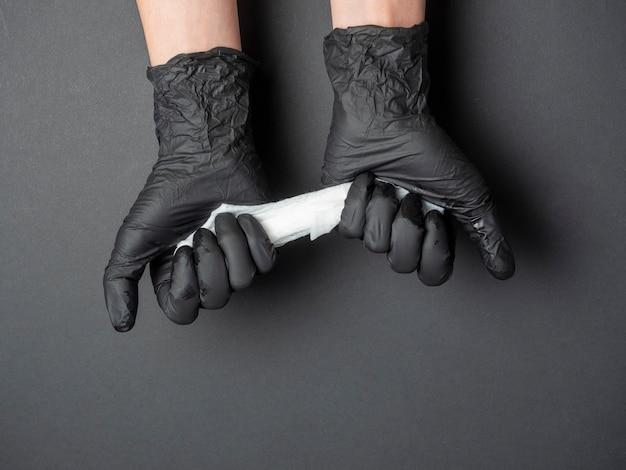 Ręce odziane w czarne lateksowe rękawiczki trzymają białą szmatę na czarnym tle