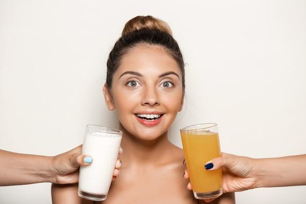 Ręce oferujące sok lub mleko młodej pięknej kobiecie