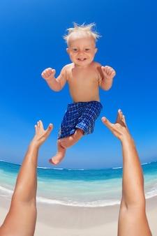 Ręce ojców wyrzucają chłopca wysoko w powietrze i łapią go