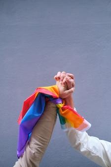 Ręce osób lgbt trzymające tęczową flagę