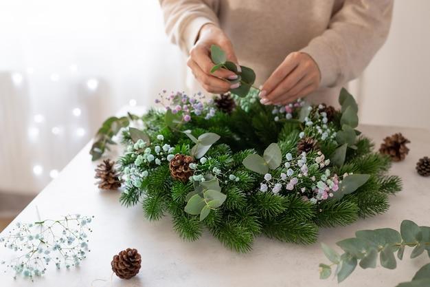 Ręce osoby co świąteczny wieniec dekoracji domu