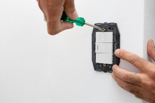 Ręce osoby mocującej śrubokrętem włącznik oświetlenia domu