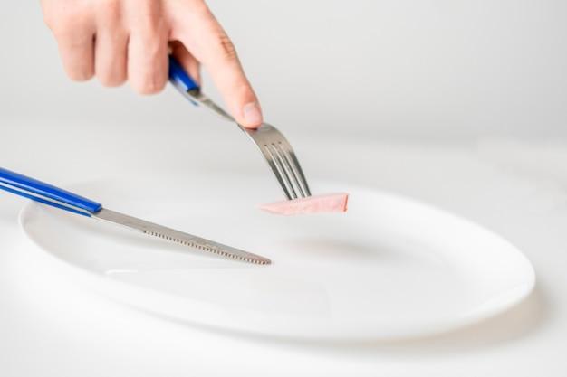 Ręce osoby z widelcem i nożem zjadają niewielką porcję jedzenia. anoreksja b