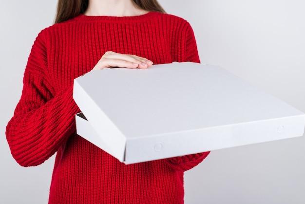Ręce otwierają papierowe pudełko z pizzą w środku