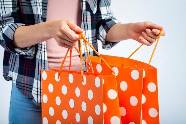 Ręce otwierające torby na zakupy w kropki