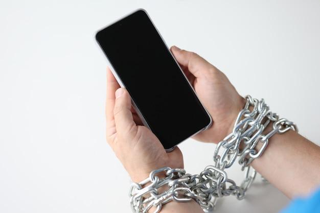 Ręce owinięte w łańcuch trzymają koncepcję uzależnienia od urządzenia mobilnego czarnego smartfona