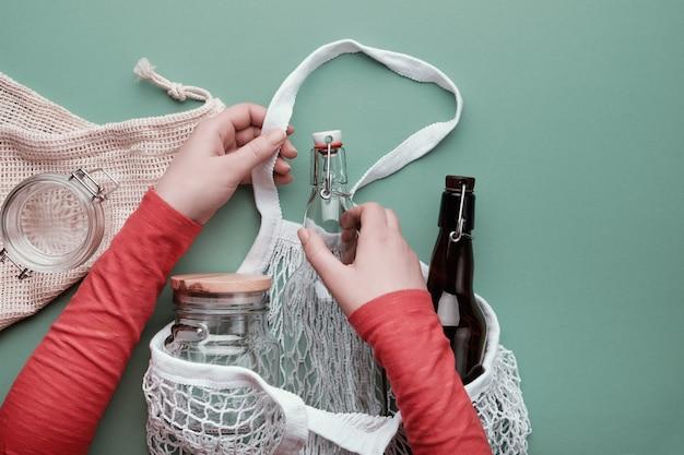 Ręce pakujące szklane butelki i słoik w siatkową torbę.