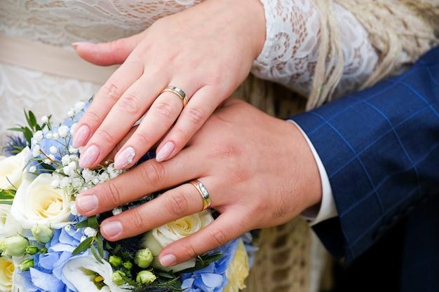 Ręce panny młodej i pana młodego na bukiet ślubny. złote obrączki na palcach nowożeńców.