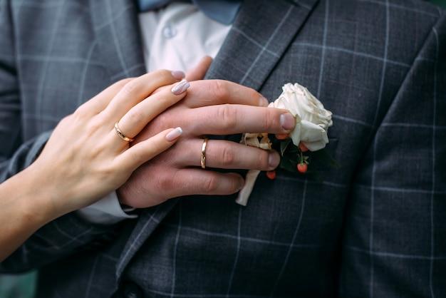 Ręce panny młodej i pana młodego z eleganckim manicure, zbliżenie. obrączki nowożeńców, para w dniu ślubu, wzruszający moment.