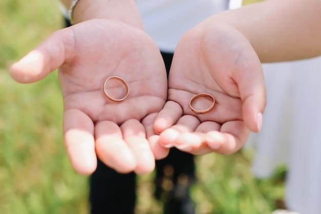 Ręce panny młodej i pana młodego ze złotymi pierścieniami. dzień ślubu, panna młoda i pan młody. szczegóły ślubu