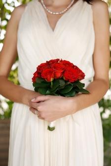 Ręce panny młodej trzymają klasyczny bukiet róż z bliska