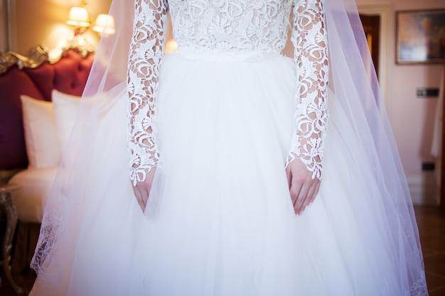 Ręce panny młodej z manicure. nadgarstek na tle białej koronki sukni pokrytej welonem