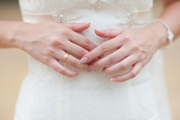 Ręce panny młodej z pierścionkiem i pięknym ślubnym manicure