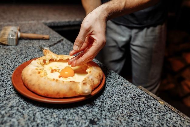 Ręce piekarza przygotowując chaczapuri na stole w kuchni