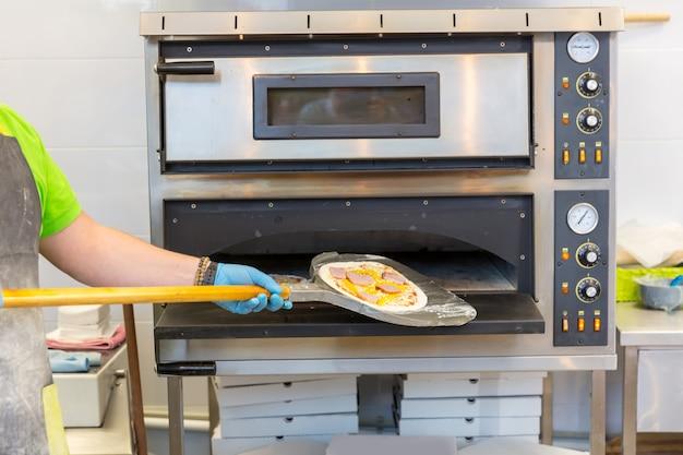 Ręce piekarza z łopatą, gotowanie pizzy, piekarniki elektryczne
