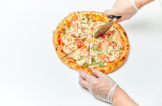 Ręce piekarzy kroją pizzę na kawałki na białym tle