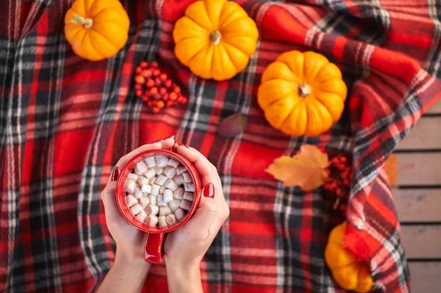 Ręce pięknej kobiety trzymającej czerwony kubek z kakao i piankami.