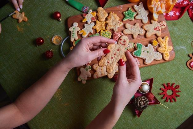 Ręce pięknej młodej kobiety trzymającej pieczonego imbirowego mężczyznę. koncepcja biesiady w domu, rodzinnego obiadu. koncepcja tradycji noworocznych i proces gotowania. tworzenie rodziny