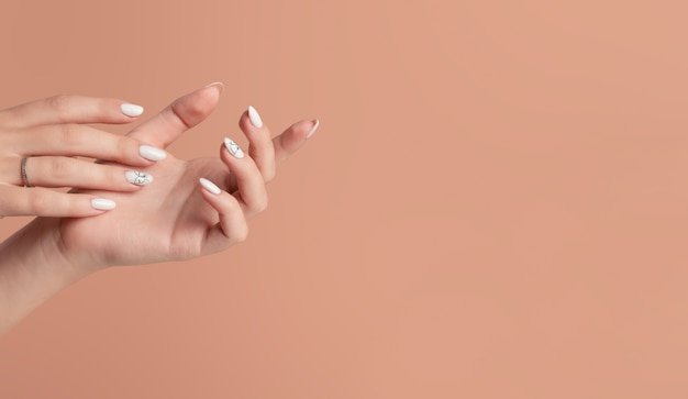 Ręce pięknej, zadbanej kobiety o kobiecych paznokciach na beżowym tle.
