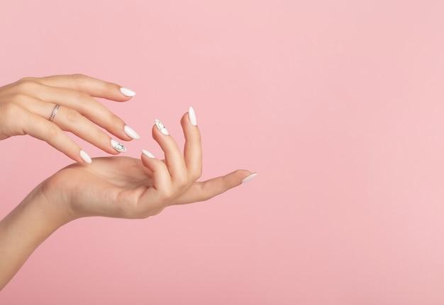 Ręce pięknej, zadbanej kobiety z kobiecymi paznokciami na różowym tle.