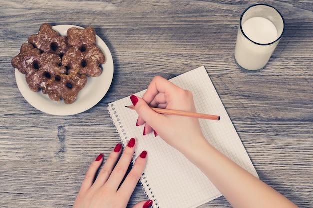Ręce, pisząc w notatniku i jedząc przekąskę