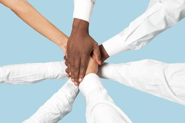 Ręce płci męskiej i żeńskiej łączące na białym tle na niebieskiej ścianie.