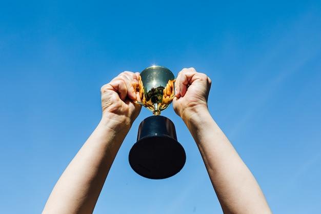 Ręce podnoszą kieliszek mistrza z niebem w tle. koncepcja zwycięstwa