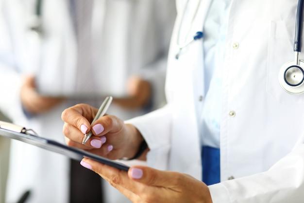 Ręce podpisania przez lekarza gp ważnego dokumentu przyciśniętego do szpitala z bliska