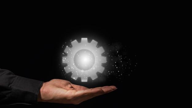 Ręce podtrzymują grafikę w kształcie koła zębatego zamiast symboli roboczych.
