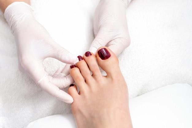 Ręce pokazują paznokcie w kolorze czerwonym.
